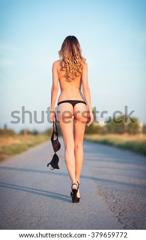 Sexy young woman in lingerie is going away by the road. Rear view. - stock photo