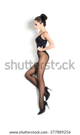 Sexy, young woman lying in alluring pantyhose over isolated background. - stock photo
