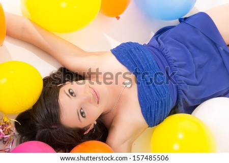 sexy young woman lying on floor among balloons - stock photo