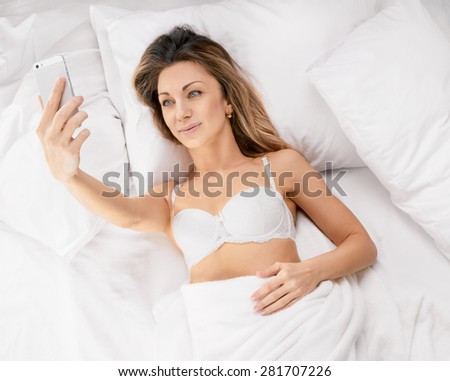 sexy young woman lying on the bed and make a selfie. Above view - stock photo
