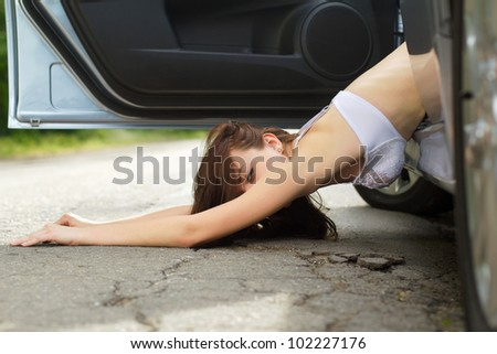 Sexy young woman lying on the road