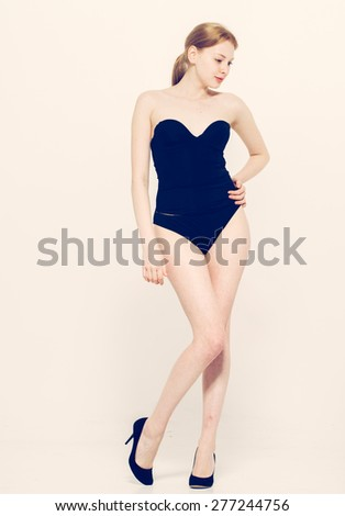 Sexy young woman posing in a black swimsuit full length isolated studio portrait, over white background