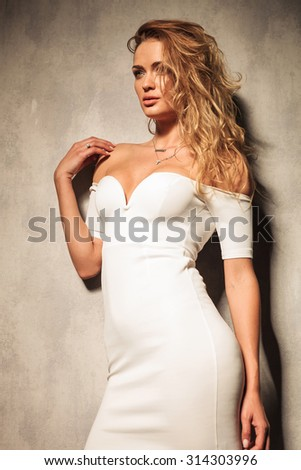 Sexy young woman posing near a grey wall, looking away from the camera. - stock photo