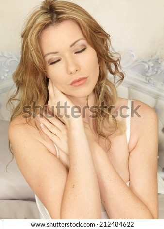 Sexy Young Woman Posing on a Bed with Neckache - stock photo