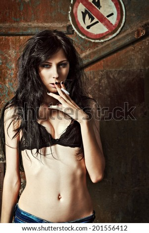 """Sexy young woman smoking cigarette near the """"No fire and smoking"""" sign - stock photo"""