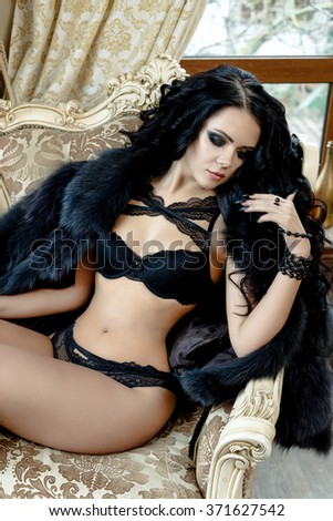 Sexy young woman wearing black lingerie with bra and panties and white black fur cloth indoors