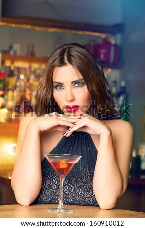 Sexy young woman with a glass of martini in a pub - stock photo
