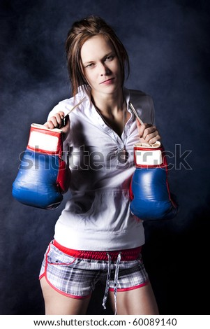 Sexy young woman with blue boxing gloves isolated on a black background with smoke behind her. - stock photo