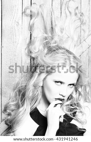 Sexy young woman with emotional pretty face and blonde curly hair closeup, black and white