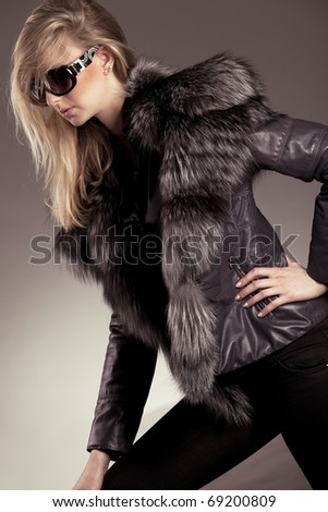 Sexy young woman with gray sunglasses and leather jacket with a hood - stock photo