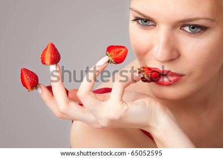 Sexy young woman with red strawberries picked on fingertips isolated on gray background