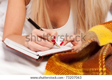 sexy young woman writing a diary while lying on the bed - stock photo