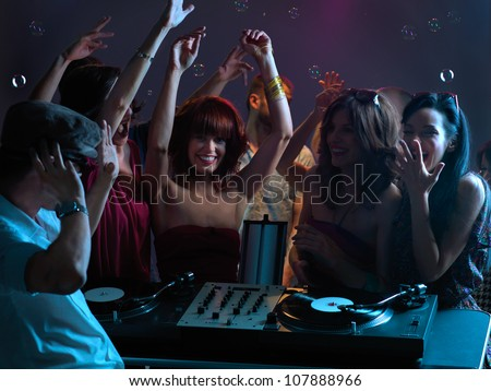 sexy, young women dancing and flirting with the dj in a night club - stock photo