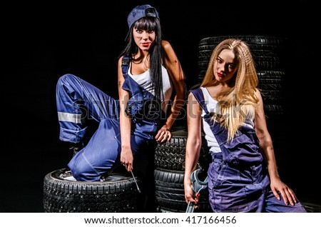 Sexy young women sitting on a tires over black background - stock photo