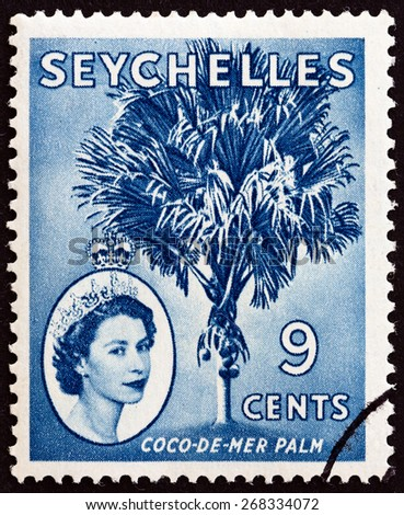 SEYCHELLES - CIRCA 1954: A stamp printed in Seychelles shows Coco-de-mer palm (Lodoicea maldivica) and Queen Elizabeth II, circa 1954. - stock photo