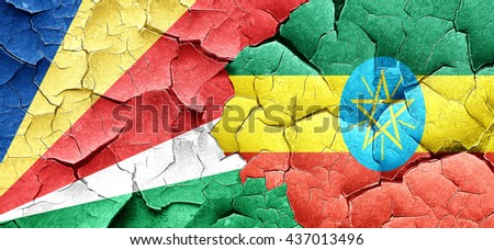 seychelles flag with Ethiopia flag on a grunge cracked wall - stock photo