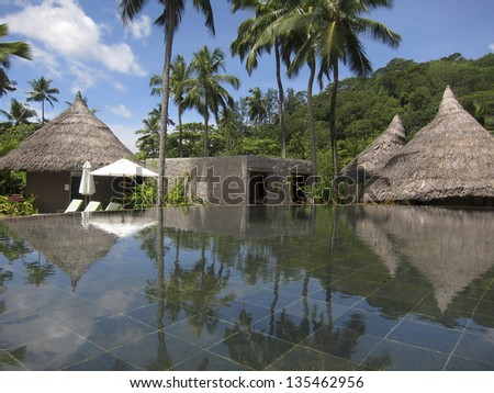 Seychelles: view of a luxury spa with a relaxing pool, jacuzzi, palm trees and sauna and hammam  (turkish or steam bath) huts - stock photo
