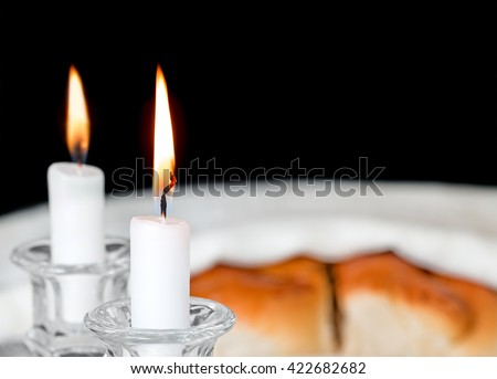 Shabbat candles in glass candlesticks with blurred covered challah background. Shallow depth of field close up. Focus on front candle flame and wick. Copyspace. Isolated on a black background.  - stock photo