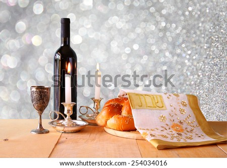 shabbat image. challah bread, shabbat wine and candelas on wooden table. glitter overlay image.  - stock photo