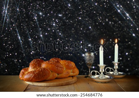shabbat image. challah bread, wine and candelas on wooden table. glitter overlay - stock photo