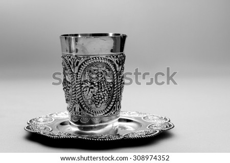 Shabbat silver kiddush cup overflowing with red wine close up. Room for text. Copy space. Isolated object. - stock photo
