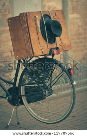 Shabby black hat and brown suitcase on old bike. Retro-style toned image - stock photo