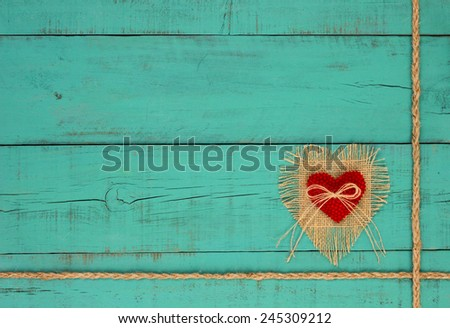 Shabby burlap, red fabric heart and braided rope border on rustic antique teal blue wooden background - stock photo
