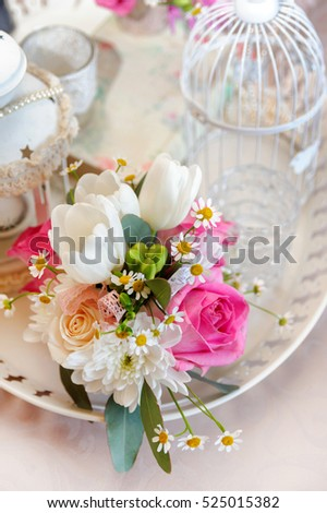 Shabby chic decoration with beautiful vintage birdcage and flowers . Wedding decor idea