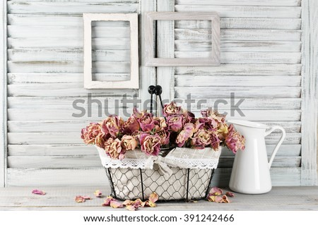 Shabby chic still life: bunch of vintage pink dry roses in wire basket and jug against white wooden blinds with empty photoframes. - stock photo