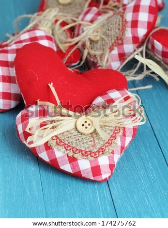 Shabby chic valentine hearts , red and white gingham cotton rustic hearts, with buttons , hessian and straw on blue wooden boards , shallow depth of field  - stock photo