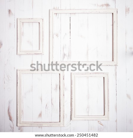 Shabby chic white frames on wooden wall - stock photo