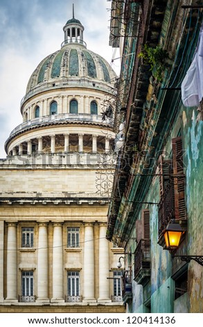 Shabby crumbling  building in Havana with the dome of the Capitol in the background - stock photo