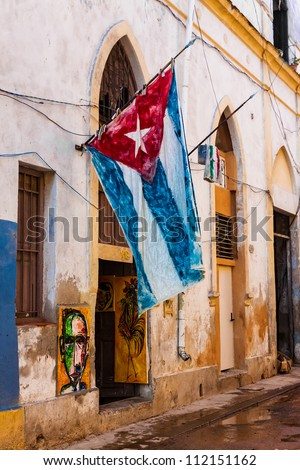 Shabby decaying house in Old Havana with a big cuban flag - stock photo
