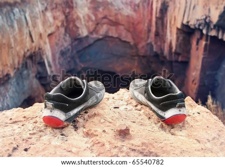 Shabby old shoes of the suicide on the brink of a precipice - stock photo