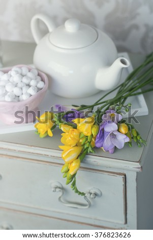 shabby shick bedside cabinet with freesias and tea pot - stock photo