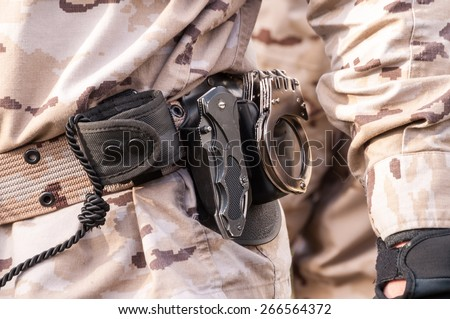 shackles belt hung a soldier dressed in camouflage - stock photo