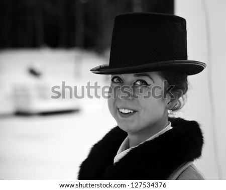Shaded portrait of smiling young woman with hat