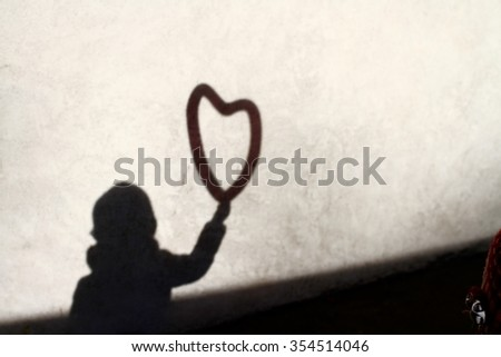 shadow and silhouette of a child bringing a heart balloon in the hand