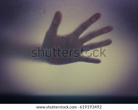 Shadow hands  behind frosted glass