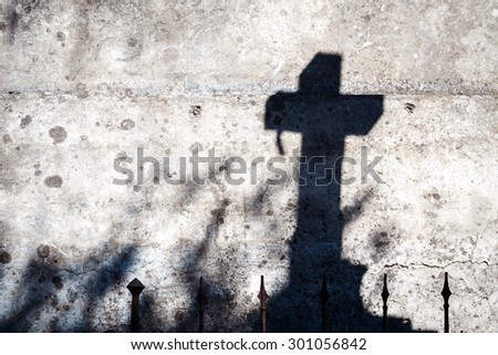 Shadow of a cross on a concrete wall - stock photo