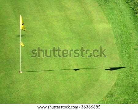 Shadow of a golf hole flag on a field - stock photo