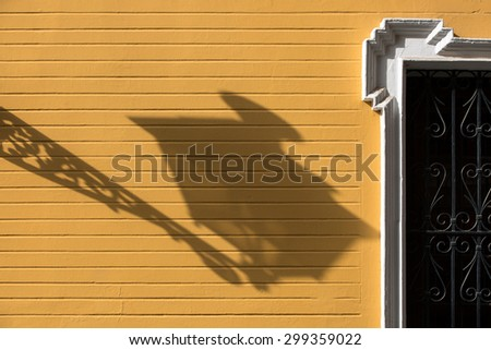 Shadow of a lamp post on a yellow wall in Seville, Spain - stock photo
