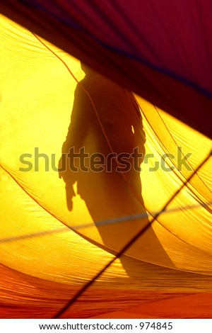 Shadow of a man projected on the inside wall of an inflating hot air balloon - stock photo