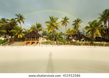 Shadow of a photographer on a sands with palm tree and rainbow in background - stock photo