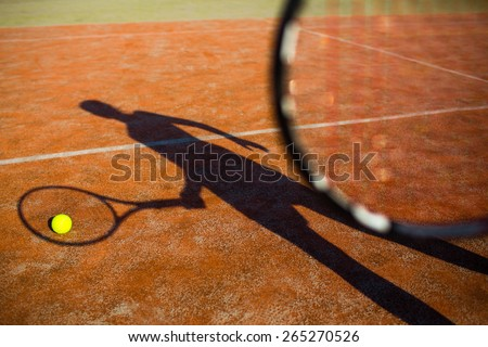 Shadow of a tennis player in action on a tennis court (conceptual image with a tennis ball lying on the court and the shadow of the player positioned in a way he seems to be playing it) - stock photo