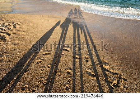 shadow of a vacationing family on the beach - stock photo