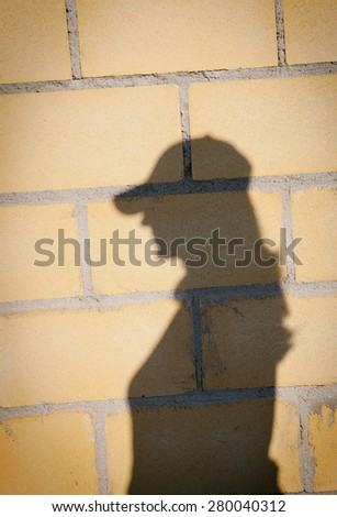 Shadow of a woman with hat on a yellow wall - stock photo