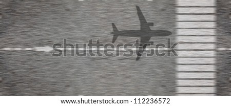Shadow of an airplane taking off from an airport runway tarmac at high speed. - stock photo