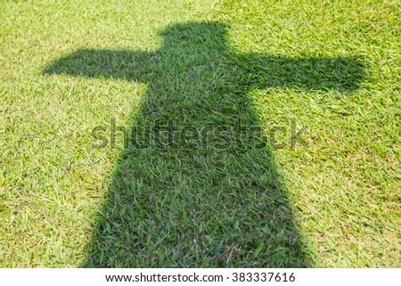 Shadow of Christian cross on green grass floor - stock photo