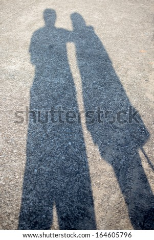 Shadow of couple on road - stock photo